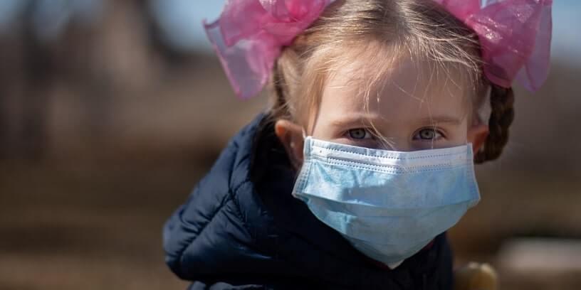 Un enfant portant un masque chirurgical