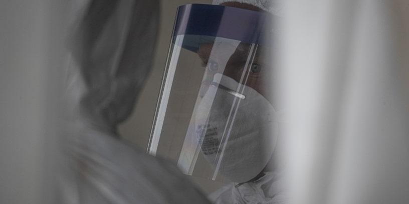 Un homme portant un masque et une visière de protection