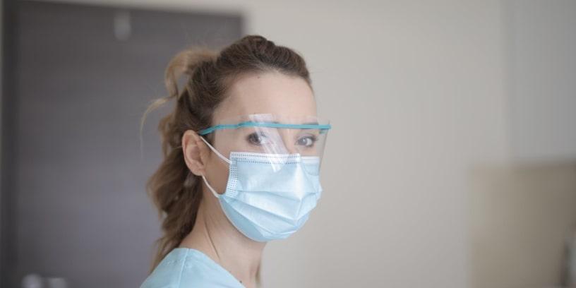 Une infirmière portant un masque chirurgical et des lunettes de protection